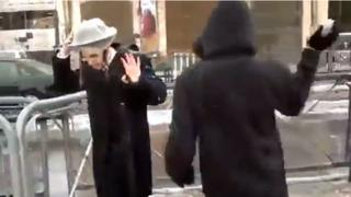 Still from YouTube footage of Palestinian throwing snow at ultra-Orthodox Jew in Jerusalem