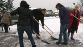 People clearing snow at The Arbours Primary School