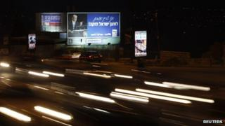 Cars drive past election posters in Jerusalem