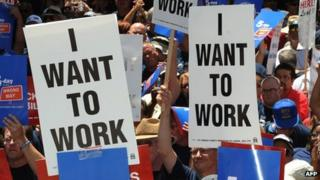 "Protesters in Los Angeles holding signs saying ""I Want to Work"". File photo"
