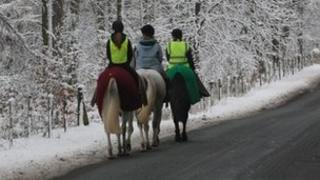 Horse riders walk below the snow covered trees surrounding the grounds close to Stourhead