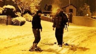 Men skiing on a road in Belfast