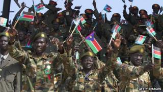 Members of South Sudan's military wave the national flag celebrating the anniversary of the country's first independence day on 9 July 2012 in Juba, South Sudan