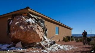 A bystander photographs a 12-by-9-foot boulder as it rests in the master bedroom of a home in St George, Utah on 19 January 2013