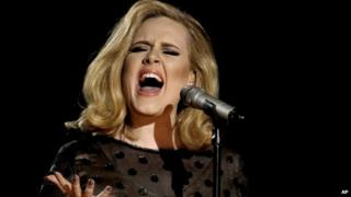 Adele singing into a microphone