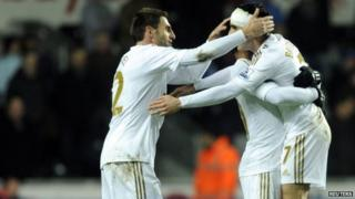 Swansea City players celebrate at the end of their match against Chelsea