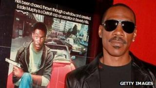 Eddie Murphy, pictured in 2010 next to a Beverly Hills Cop poster