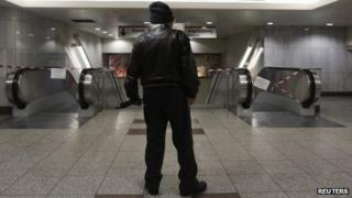 A commuter stands in front of closed escalators at a metro station in Athens, 24 January 2013