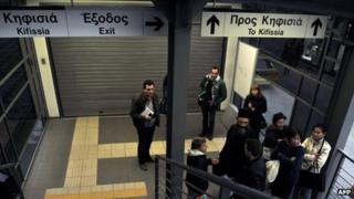 Commuters talk at the closed entrance to an urban rail station in Athens on January 24