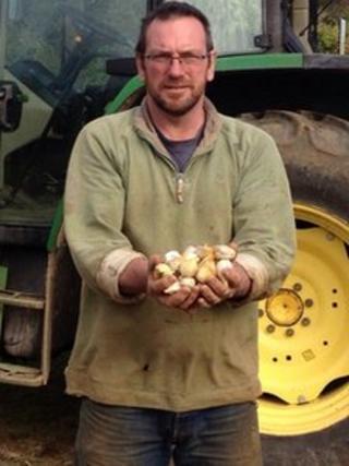 Mark Botwright holding bulbs of garlic