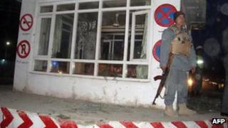 An Afghan policeman stands guard at the site of a suicide attack in Kunduz