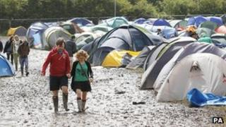 Festival-goers walk through the mud at the campsite at the Isle of Wight Festival on the Isle of Wight