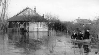 A policeman and rescue worker rowing a flood victim from her home at Canvey Island, Essex