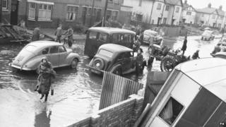 A woman is carried along a flooded street in the Wansbeck road area in King's Lynn in 1953