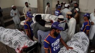 Relatives gather around the body of Abdul Majeed Deenpuri