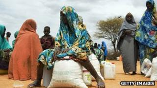 Women sit with their food rations