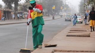 A street cleaner - wearing Ghanaian football colours - in Kumasi in 2008