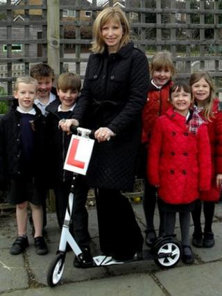 Head teacher on scooter surrounded by pupils