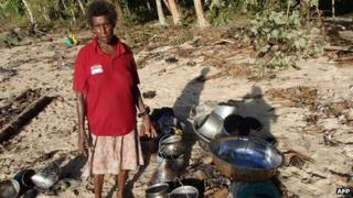 A resident with salvaged possessions from her destroyed home in the village of Venga, Solomon Islands, on 7 February 2013