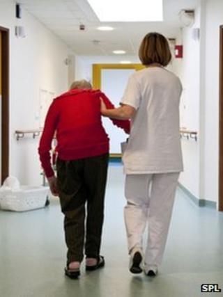 An elderly patient is helped by a nurse