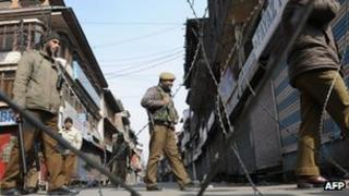 Indian police patrol a deserted street in Srinagar