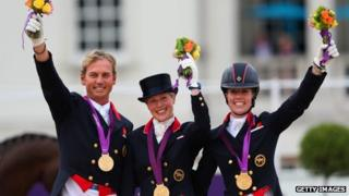 Carol Hester, Laura Bechtolsheimer and Charlotte Dujardin of Team GB celebrate with their gold medals