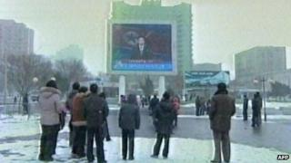 Screen grab from North Korean TV showing television announcement of nuclear test to people at Pyongyang's railway station on 12/2/13
