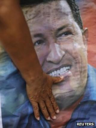 A supporter of Venezuelan President Hugo Chavez touches a poster of him at a local election rally, December 2012