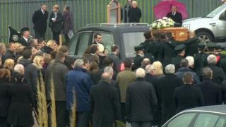 Pall bearers carry coffin behind hearse