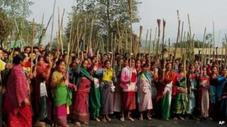 Members of the Rabha tribe stand with sticks and brooms block a road protesting a local government election in Goalpara district, 120 kilometers (75 miles) from Gauhati, capital of the northeastern Indian state of Assam, Tuesday, Feb. 12, 2013.