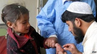 Pakistani paramedics treat an injured girl after the roadside bomb attacks on pro-government militia, at a hospital in Kohat