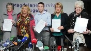 Members of the Magdalene Survivors Together campaign group hold copies of the report