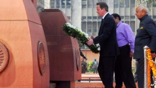 British Prime Minister David Cameron walks to lay a wreath at the site of a notorious 1919 massacre of hundreds of Indians by British colonial forces, in Amritsar, India, Wednesday, Feb. 20, 2013