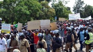 Escorted by heavily armed riot police, people march on the streets of Blantyre on 17 January 2013 to protest against government's IMF backed tough reforms designed to right the economy and win back investors