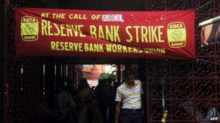 Indian employees stand near posters at the entrance to a bank during a two-day strike opposing the current UPA government's economic policies in Kolkata