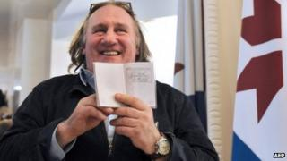 French actor Gerard Depardieu holds his passport registration