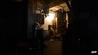 A Pakistani man preparing tea at his restaurant during a nationwide power blackout in Karachi, 24 February 2013