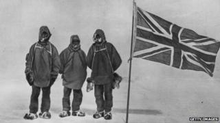 Irish explorer Sir Ernest Henry Shackleton and two members of his expedition team beside a Union Jack within 111 miles of the South Pole.