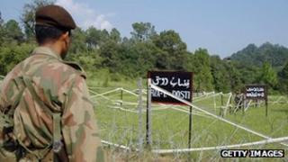 A Pakistani soldier watches Indian soldiers at the Tattapani-Mendher crossing point on the Line of Control, some 35km from Kotli, in Pakistani administered Kashmir, 09 September 2006