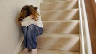 Young girl sits on a staircase and covers her face.