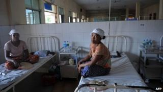 """This picture taken on February 27, 2013 shows injured villagers sitting on beds at a hospital in Maubin, in Myanmar""""s Delta region, following clashes with police."""