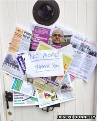 """Dozens of leaflets pinned to a front door under a note saying """"no more thank you""""."""