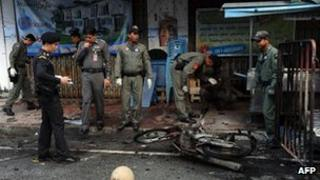 Members of a Thai bomb squad inspect the site of a motorcycle bomb blast triggered by suspected separatist militants in front of a market in Thailand's restive southern province of Narathiwat, 1 March 2013