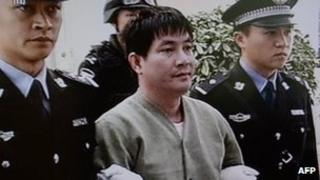 Convicted murderer Naw Kham is led from his cell in Yunnan, China (1 March 2013)