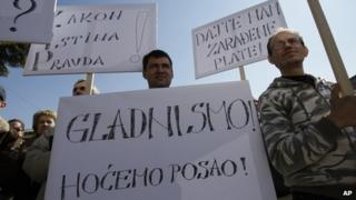 "People hold up banners saying ""we are hungry"", ""we want jobs"" and ""we want our salaries"" in front of a municipality building in Drvar, Bosnia-Hercegovina (4 March 2013)"