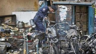 """An official of India""""s National Investigation Agency looks for evidence in the debris at one of the two bomb blast sites, in Hyderabad, India, Friday, Feb. 22, 2013"""
