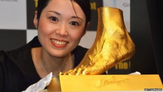 Woman poses with Golden statue of the left foot of Lionel Messi.