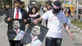 Palestinian demonstrators hold posters depicting of late president Hugo Chavez during a protest outside Israel's Ofer military prison near the West Bank city of Ramallah, in support of hunger striking Palestinian detainees held in Israeli jails