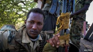 A soldier of the Somali National Army (SNA) rests on a bridge 7km (4 miles) east of the central Somali town of Buur-Hakba