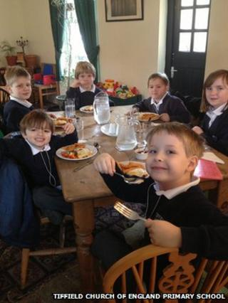 Children sat at table with dinner